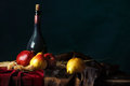 A bottle of old wine and ripe fruit on a dark background, Dutch still life. Royalty Free Stock Photo