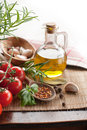 Bottle of olive with tomatoes oil garlic condiments and basil on a wooden table Stock Photography