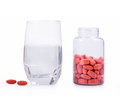 Bottle of pills and glass of water on white background Royalty Free Stock Photos