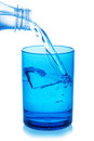 Bottle pouring water into glass on white background. Royalty Free Stock Photo