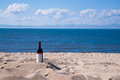 Bottle with red wine on the beach in a summer sunny day. Yellow sand, white clouds, blue sky and blue sea in the Royalty Free Stock Photo