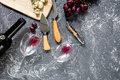 Bottle of red wine with cheese and grape aperitive on grey stone table background copyspace top view