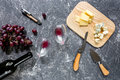 Bottle of red wine with cheese and grape aperitive on grey stone table background top view