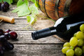 Bottle of red wine and fresh grape on wooden table Stock Photography