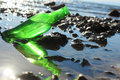 A bottle by the sea on beach with rocks Stock Images