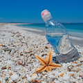 Bottle sea star and sun of water on white pebbles under a shining Royalty Free Stock Photography
