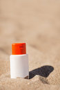 Bottle of sun block creme on sand Royalty Free Stock Photos