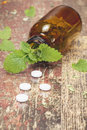 Bottle with tablets and herbal on wooden table homeopathic medication alternative medicine pills macro close up Stock Photography