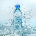 Bottle of water splash on a blue background Stock Photo