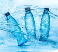 Bottle of water splash on a blue background Stock Photo