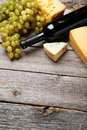 Bottle of white wine cheeses and grapes on the grey wooden background Stock Image