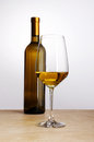 Bottle of white wine with glass flat on the table brown Royalty Free Stock Photos