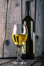 Bottle of white wine and wineglass on wood backround vintage photo old Stock Images