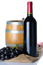 Bottle of wine with black grapes and a cask on a burlap bag isolated white Stock Photography