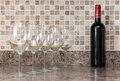 Bottle of wine and glasses on kitchen countertop red empty Royalty Free Stock Image