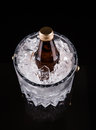 Bottled drink and ice bucket iii a bottle of refreshing chilled in an over black background Royalty Free Stock Photo
