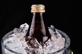 Bottled drink and ice bucket viii a bottle of refreshing chilled in an over black background Stock Photography