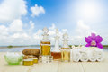 Bottles of aromatic oils with candles, pink orchid, stones and white towel on wooden floor on blurred lake with cloudy sky Royalty Free Stock Photo