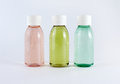 Bottles with colored liquids three plastic on white background Stock Images