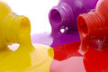 Bottles of colorful paint closeup spilled on white background Stock Image