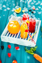 Bottles of fresh squeezed citrus and berry juice freshly homemade with a jug iced carrot orange blend served on a wooden Royalty Free Stock Image