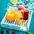 Bottles of freshly squeezed orange and berry juice standing on a wooden tray on a colorful turquoise blue picnic table in dappled Royalty Free Stock Photos