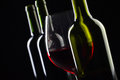 Bottles and glass of red wine on a black background .