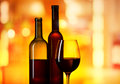Bottles and glass with wine on orabge background Stock Photography