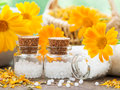 Bottles of homeopathy globules and marigold flowers. Royalty Free Stock Photo