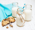 Bottles of milk and cookies on a old white wooden background Stock Photography