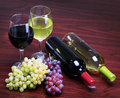 Bottles of red and white wine with fresh grapes glasses of wine on the table Royalty Free Stock Images