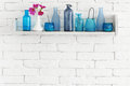 Bottles on a shelf decorative white brick wall with blue it Royalty Free Stock Image