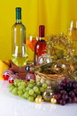 Bottles of wine with grapes and christmas decorations on a white top yellow cloth background Stock Image