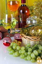 Bottles of wine with grapes and christmas decorations on a white top yellow cloth background Royalty Free Stock Photo