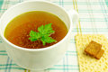 Bouillon broth clear soup in a white cup with a loaf parsley on the tablecloth close up Stock Photography