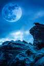 Boulder against blue sky with clouds and beautiful full moon at Royalty Free Stock Photo