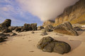 Boulders on sandy beach and coastal cliffs island vaeroy lofoten islands in norway Stock Image