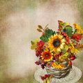 Bouquet of autumn flowers, leaves and berries in a wicker basket on a vintage background Royalty Free Stock Photo