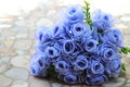 Bouquet of blue rose lying on grey road Royalty Free Stock Photo