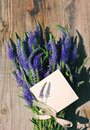 Bouquet of blue wild summer flowers and white empty card for an inscription Royalty Free Stock Photo