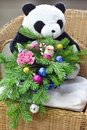 Bouquet of Christmas tree with Christmas decorations and lovely flowers. On a wicker chair. Toy bear in the background