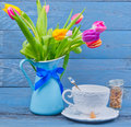 Bouquet colorful tulips blue jug next cup tea blue wooden table Stock Photography