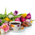 Bouquet of colorful tulips and tea cup full of tea isolated on white Stock Image