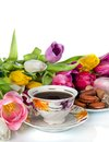 Bouquet of colorful tulips and tea cup full of tea isolated on white background Stock Images