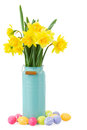 Bouquet of daffodils flowers with easter eggs yellow in blue vase on white background Stock Photos