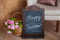 Bouquet of flowers in a basket and words happy easter on blackboard