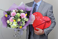 Bouquet of flowers and box of chocolates businessman holding a a red heart shape Royalty Free Stock Photo