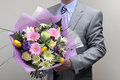 Bouquet of flowers businessman wearing a suit holding a Royalty Free Stock Images