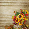 A bouquet of flowers, leaves and berries in a wicker basket on a wooden background Royalty Free Stock Photo