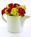 Bouquet of flowers in teapot red roses and yellow white studio background Royalty Free Stock Photography